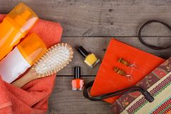 Hairbrush, orange towel, sun cream, lotion, beach bag, nail polish, a book on a brown wooden background. Beach accessories - hairbrush, orange towel, sun cream stock photography