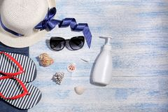 Beach accessories. Hat, flip flops and cream on a blue wooden background. Beach accessories. Hat, flip flops and cream with seashells on a blue wooden stock image