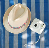 Beach accessories. Hat, Instant camera and deck chair. Male hat and Instant camera on the striped deck chair Royalty Free Stock Images