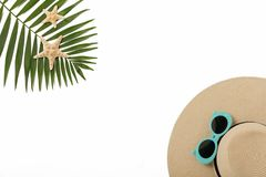 Beach accessories hat and sunglasses blue color with tropical pa. Lm leaves on white background with empty space for text.  Flat lay, top view Stock Image