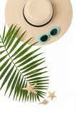 Beach accessories hat and sunglasses blue color with tropical pa. Lm leaves on white background with empty space for text.  Flat lay, top view Royalty Free Stock Images