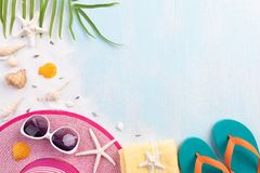 Beach accessories including flip flop, starfish, beach hat and sea shell on sandy beach and blue wooden background for summer stock image
