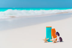 Beach accessories needed for sun protection. Suncream bottles, goggles, starfish on white sand beach background ocean Royalty Free Stock Image