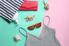 Free Beach Accessories On A Colored Pastel Background. Beach Bag, T-shirt, Sunglasses, Purse, Sunblock, Cockleshells. Top View. Royalty Free Stock Images - 135522269