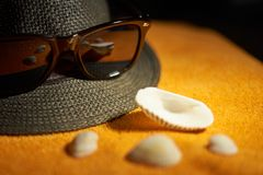 Sun glasses, striped hat and sea shells on an orange towel. royalty free stock images