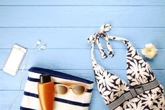 Beach accessories and phone on blue wooden background Royalty Free Stock Image
