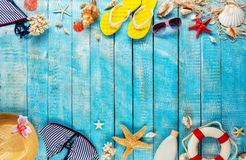 Beach accessories placed on blue wooden planks, top view. Royalty Free Stock Photos