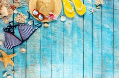 Beach accessories placed on blue wooden planks, top view. Stock Image