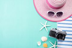 Beach accessories retro film camera, sunglasses, flip flop starfish beach hat and sea shell on green pastel background for summer stock image