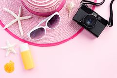 Beach accessories retro film camera, sunglasses starfish, beach hat and sea shell sunblock on sandy beach and pink background for royalty free stock images