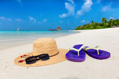 Beach accessories on sand, clear turquoise ocean in Maldives. Vacation, travel concept. Sunglasses, flip-flops and sunhat royalty free stock image