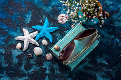 Beach accessories. Seashells, sunglasses and starfish on a dark blue background. With copy space. Stock Image
