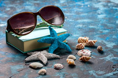 Beach accessories. Seashells, sunglasses and starfish on a dark blue background. With copy space. Travel and adventure concept Stock Images