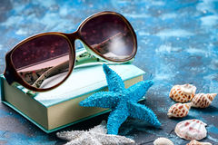 Beach accessories. Seashells, sunglasses and starfish on a dark blue background. With copy space. Travel and adventure concept Royalty Free Stock Photo