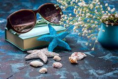 Beach accessories. Seashells, sunglasses and starfish on a dark blue background. With copy space. Travel and adventure concept Stock Photography