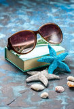 Beach accessories. Seashells, sunglasses and starfish on a dark blue background. With copy space. Travel and adventure concept Stock Photo