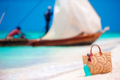 Beach accessories - straw bag, sunscreen bottle and red sunglasses on the beach Royalty Free Stock Image