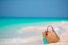 Beach accessories - straw bag, white hat and red sunglasses on the beach Royalty Free Stock Image