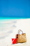 Beach accessories - straw bag, white hat and red sunglasses on the beach Stock Photos