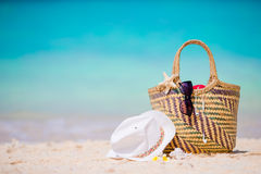 Beach accessories - straw bag, white hat, starfish and black sunglasses on the beach. Summer beach concept Stock Images