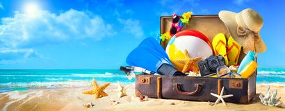 Beach accessories in suitcase on sand. Family holidays concept. Preparation for summer vacation. Beach accessories in suitcase on sand. Family holidays concept royalty free stock images