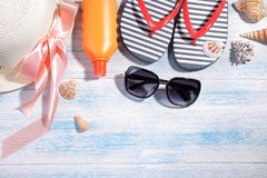 Beach accessories. summer hat , cream, black glasses and sea shells on a blue wooden background. Top view Stock Photos