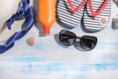 Beach accessories. summer hat with flakes, cream, glasses and sea shells on a blue wooden background. Top view Royalty Free Stock Photos