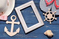 Beach accessories. A summer hat with flip flops, a wooden frame, a wooden anchor and a steering wheel on a blue background. Top vi. Ew royalty free stock images