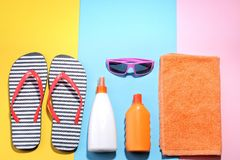 Beach accessories. Various creams, glasses, flip flops and on a colored background. Top view. Beach accessories. Various creams, glasses, flip flops and a towel stock photos