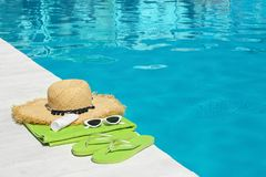 Beach accessories on wooden deck near swimming pool. Space for text stock image