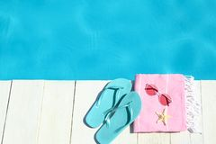 Beach accessories on wooden deck near swimming pool. Space for text stock images