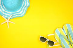 Summer vacation beach accessories border on a yellow background with copy space stock photography
