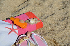 Beach Accessorize on Sandy Beach. White hat, flip flops, colorful towel, sun lotion, starfish and shells on beach with sea Stock Image