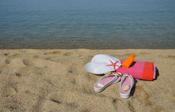 Beach accessorize on sandy beach. White hat, flip flops, colorful towel, sun lotion, starfish and shells on beach with sea in background Stock Images