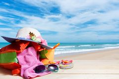 Beach accessory,sunglasses, flip-flops, hat, cloths, on wooden floo Stock Photos