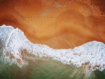 Beach on aerial drone top view with ocean waves reaching shore.  royalty free stock photography