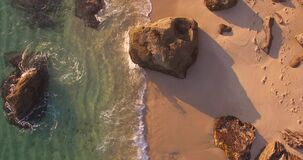 Beach Aerial Top Shot On the Sunset with waves crashing sand rocks. With nice colors stock video footage