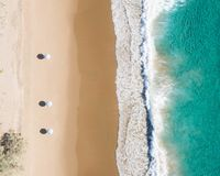 Beach aerial view of umbrellas, waves, blues ocean and relaxing vibes stock photography