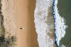 Beach aerial view of umbrellas, waves, blues ocean and relaxing vibes royalty free stock photos