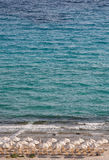 Beach in Afitos, Halkidiki, Greece. Beach on the shore of the sea with sun beds and parasols Royalty Free Stock Photo