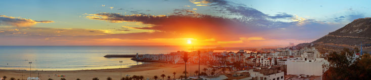 Beach in Agadir city at sunset, Morocco. Panorama view of long, wide beach in Agadir city at sunset, Morocco. The hill bears the inscription in Arabic: God Stock Image