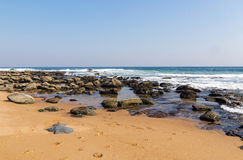 Beach Against Rocky Ocean Shoreline and Blue Sky Landscape. Coastal landscape view of sandy beach against rocky ocean shoreline and blue sky in South Africa Stock Photography