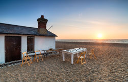 The Beach at Aldeburgh. A table and chairs at sunrise on the beach at Aldeburgh in Suffolk Stock Photos