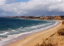 Beach in the Algarve region of Portugal. People swimming and surfing. Pine trees at foreground.  A view from the top. Royalty Free Stock Photos
