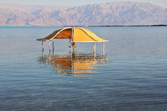 The beach arbor. Solar beach on the Dead Sea. Wonderful warm day in December. The beach arbor is half flooded by the risen sea water Stock Photography