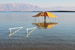The beach arbor is half flooded. Solar beach on the Dead Sea. Wonderful warm day in December. The beach arbor is half flooded by the risen sea water Royalty Free Stock Photography