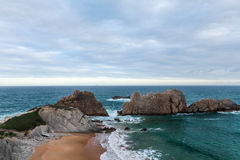 The beach of Arnia in Liencres , Cantabria, Spain. The picture represents a landscape of the Cantabrian coast, beach Arnia in Liencres. The sea, blue cloudy sky Stock Image
