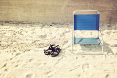 Beach attributes. Sandals and armchair on the beach Stock Photo