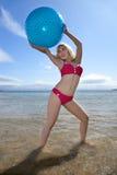 Beach Babe. Teenager in red bikini sat in orange deckchair on beach royalty free stock image
