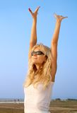 Beach babe. Lovely blond raising hands to the sun Stock Photo